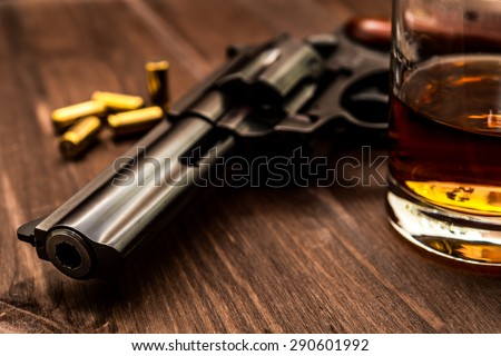 Glass of whiskey with revolver on the wooden table. Close up view, focus on the barrel of revolver - stock photo