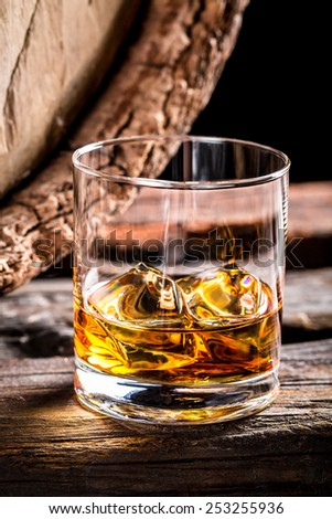 Glass of whisky and old oak barrel - stock photo