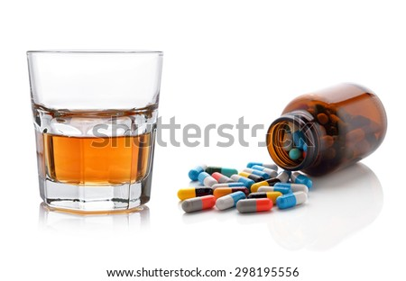 Glass of whisky and pills capsules on white background. - stock photo