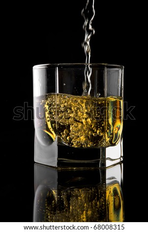 Glass of whisky on a black background. - stock photo