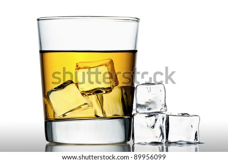 glass of whisky on the rocks with ice cubes next to, isolated on white - stock photo