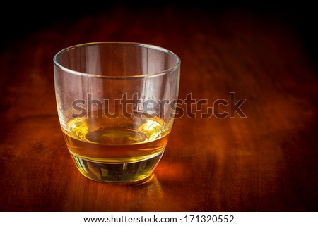 Glass of whisky or rum on a wooden table (with beautiful golden lighting) - stock photo