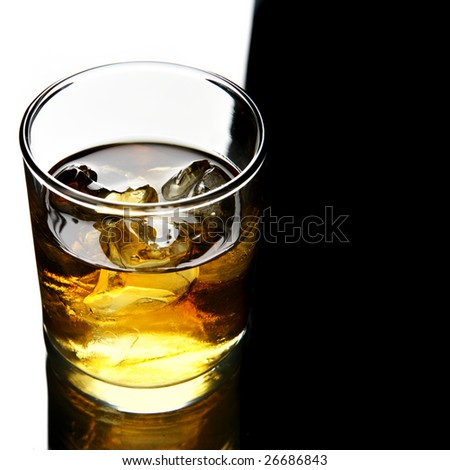 Glass of whisky with ice with space for text on right - stock photo
