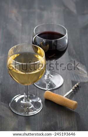 glass of white and red wine on a dark wooden background, vertical - stock photo