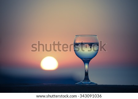 Glass of white vine with reflections of houses and view to beautiful sunset. Selective focus. Toned. - stock photo