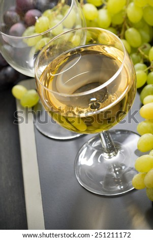 glass of white wine and grapes on a blackboard, close-up, vertical