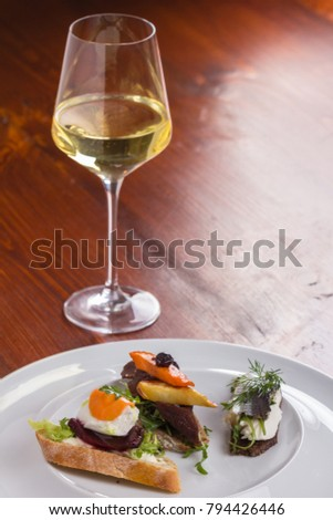 Glass of white wine and tartines with meat and veggies.