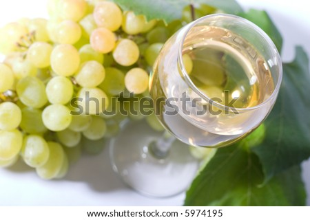 glass of white wine and white grapes. Low DOF, focal point is on wine