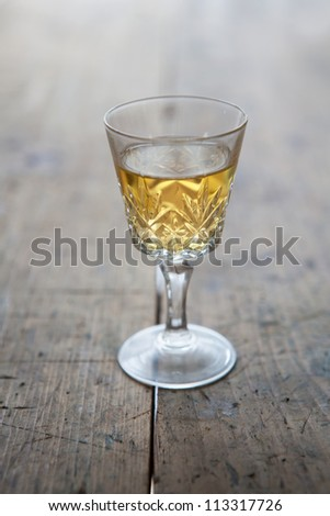 Glass of white wine in a antique glass, placed on a old wooden table. - stock photo