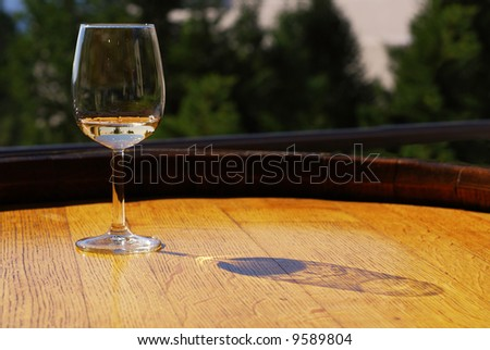 Glass of white wine on a wooden barrel - stock photo