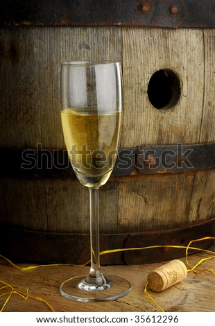Glass of white wine on background of old wine barrel - stock photo