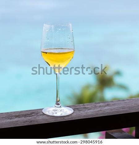 Glass of white wine on balcony rail, Tropical view  - stock photo