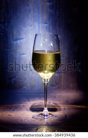 Glass of white wine on blue old wooden background - stock photo