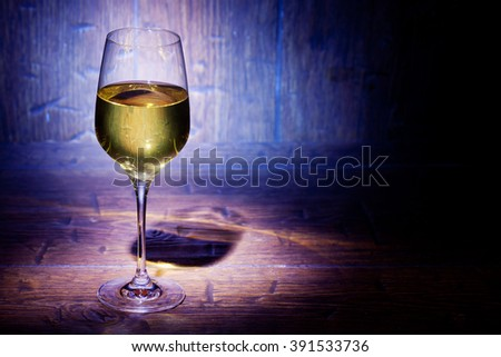 Glass of white wine on blue old wooden background with place for text - stock photo