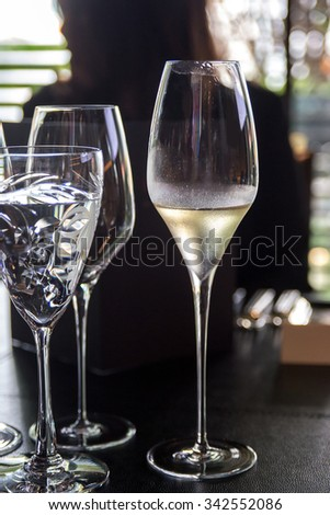 Glass of white wine on restaurant table - stock photo