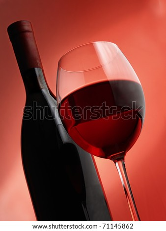 Glass of white wine on the blurred bottle background