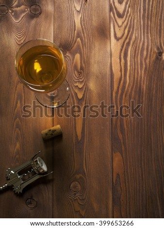 Glass of white wine on the wooden table. Top view