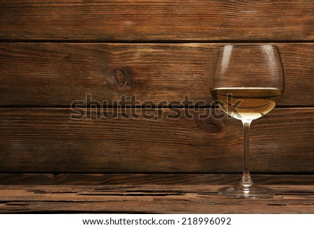 Glass of white wine on wooden table on wooden wall background