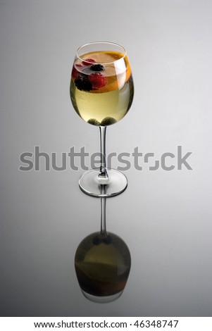 Glass of white wine sangria on grey background with reflection - stock photo