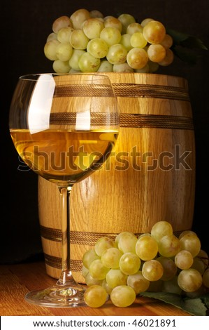 Glass of white wine, white grape and souvenir barrel on wooden surface. - stock photo