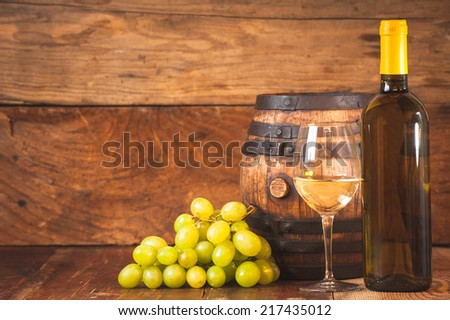 Glass of white wine with bottle and barrel on a rustic wooden table