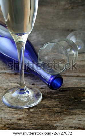 Glass of white wine with wine bottle and another glass that has been spilled.  Special lighting to add to the mood of the image. - stock photo
