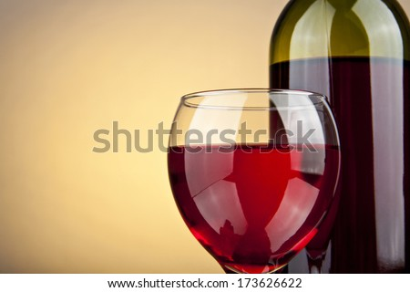 glass of wine and a bottle on a yellow background - stock photo