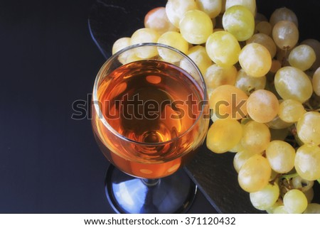glass of wine and a bunch of grapes dessert - stock photo