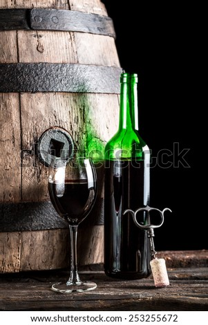 Glass of wine and bottle in the old cellar - stock photo