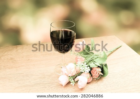 glass of wine and flower on blur bokeh from bush background - stock photo