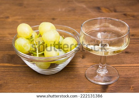 Glass of wine and grapes on bowl on wooden table