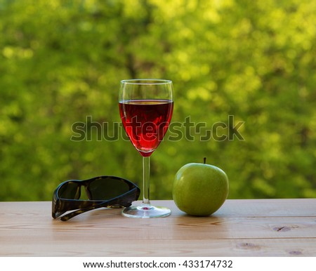 glass of wine green apple and sunglasses on table in the garden - stock photo