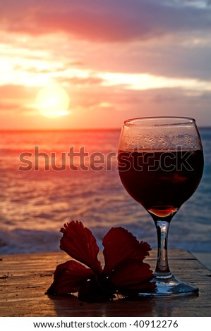 Glass of wine on the see shore with a flower - stock photo