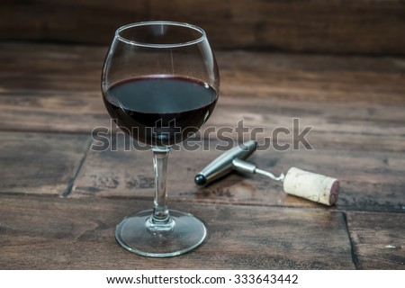 glass of wine with a corkscrew - stock photo