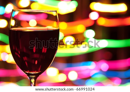 Glass of wine with blured motion lights in the background - stock photo