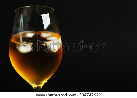 Glass of wine with ice cubes on dark background