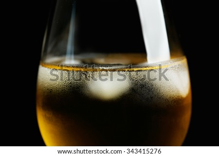 Glass of wine with ice cubes on dark background - stock photo