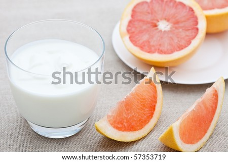 Glass of yogurt with segments of pink grapefruit