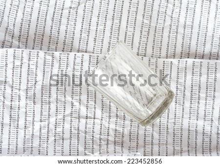 Glass on a background of crumpled DNA sequence - stock photo