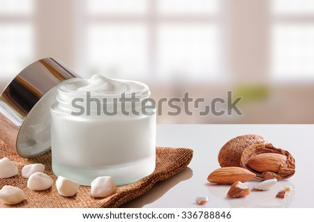 Glass open jar with facial or body almond moisturizer on burlap. With lid, small stones and almonds. Windows background. Front view. - stock photo