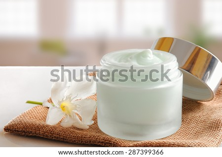 Glass open jar with facial or body cream on burlap. With lid and flower.Windows background. Front view. - stock photo