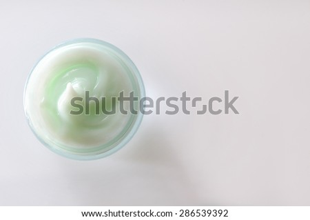 Glass open jar with facial or body cream on white table. Top view. White isolated. - stock photo
