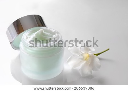 Glass open jar with facial or body cream on white table with flower. Top view. White isolated. - stock photo
