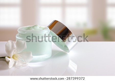 Glass open jar with facial or body cream on white table. with lid and flower. Background windows. Front view. - stock photo
