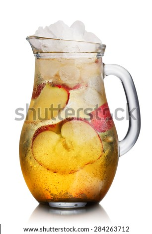 Glass pitcher of homemade spritzer (apfelschorle) served with crushed ice and apple slices. Jug full of non-alcoholic sparkling and cold carbonated apple juice. - stock photo
