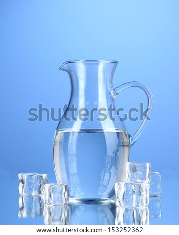Glass pitcher of water on blue background - stock photo