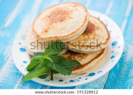 Glass plate with homemade fritters over blue wooden background - stock photo