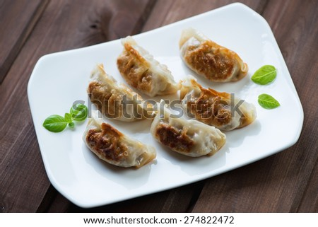 Glass plate with pan fried japanese gyoza dumplings, studio shot - stock photo