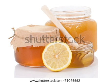 glass pot full of honey and lemon isolated on white background - stock photo