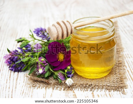 Glass pot of sweet honey with flowers on wooden table - stock photo
